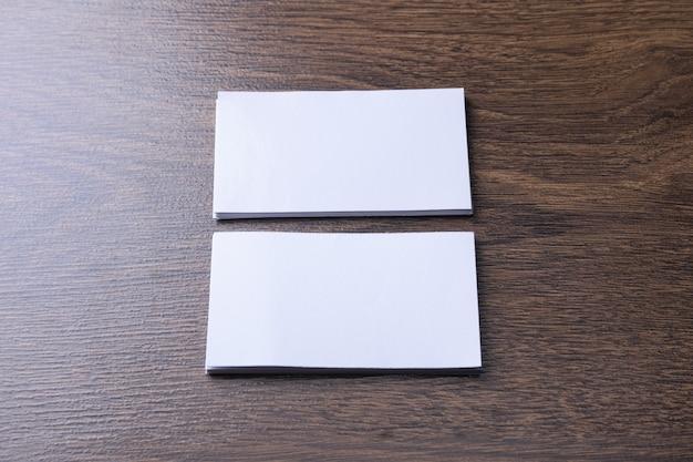 Visitekaartje leeg op houten achtergrond. corporate briefpapier, merkmodel. creatief designbureau. plat leggen. kopieer ruimte voor tekst. sjabloon voor id. Premium Foto