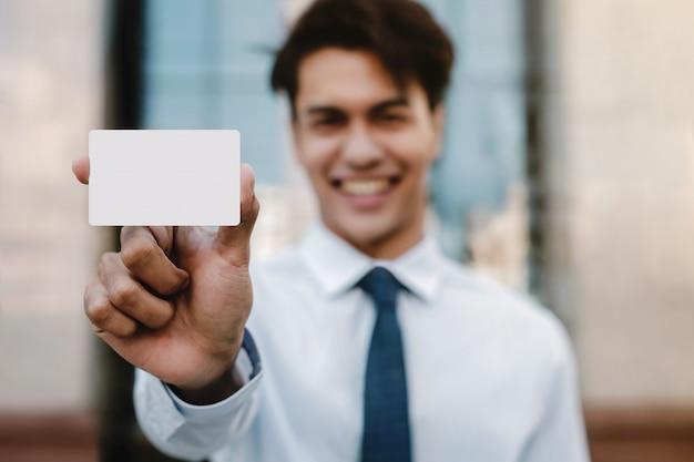Visitekaartje mockup afbeelding. gelukkig jonge zakenman presenteren een witte blanco papier kaart met uitknippad Premium Foto