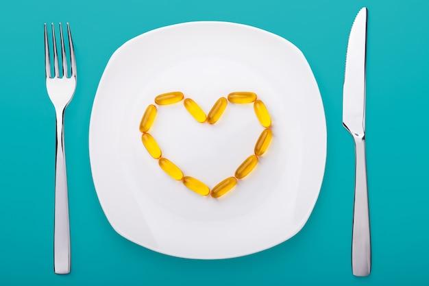Visolie zachte gels liggend op een witte porseleinen plaat in de vorm van een hart Premium Foto