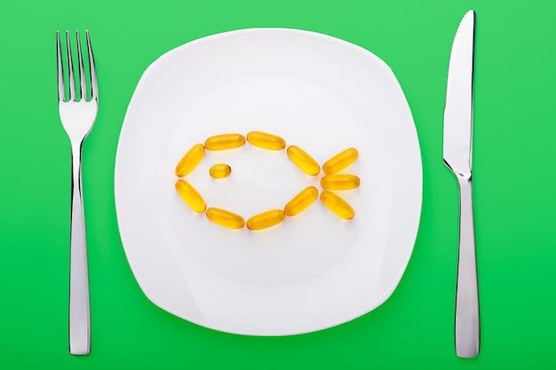 Visolie zachte gels liggend op een witte porseleinen plaat in de vorm van vis Premium Foto