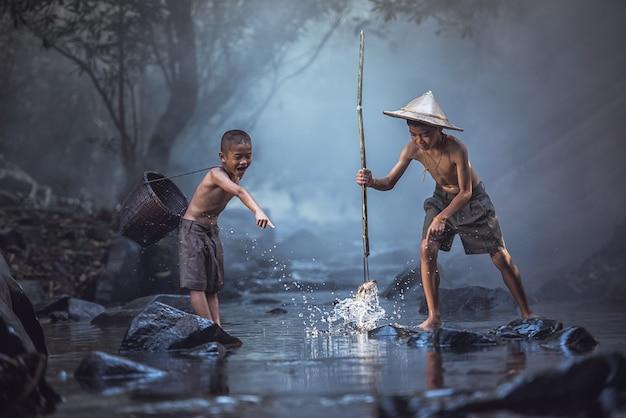 Vissende jongens die in de rivier, platteland van thailand vissen. Premium Foto