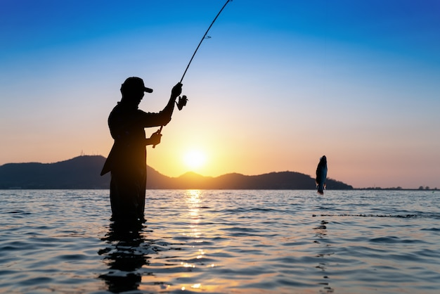 Visser die zijn staaf werpt, die in het meer, de mooie scène van de ochtendzonsondergang vissen. Premium Foto