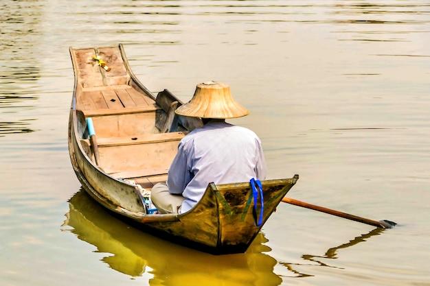 Visser in een aziatische kegelhoed die in het meer met een kleine houten boot vaart Gratis Foto