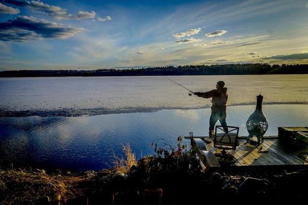 Visser op een pijler die vissen vangt tijdens een zonnige mooie dag Gratis Foto