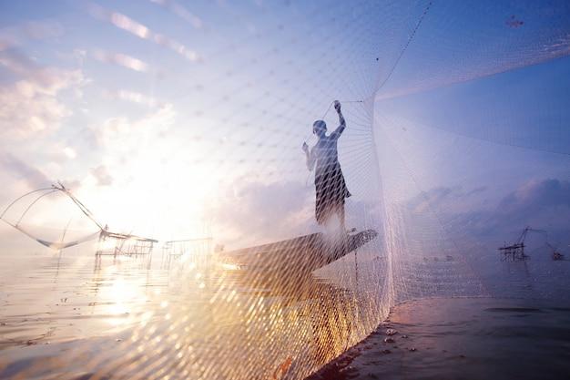 Vissers op boot vissen met een groot visnet. silhouet scène van de ochtend. Premium Foto