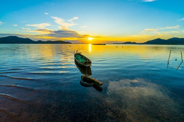 Vissersboot met zonsondergang bij het reservoir van klappra, sriracha chon buri, thailand Premium Foto