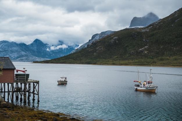 Vissersboten zeilen in het meer in de buurt van de bergen onder de bewolkte hemel Gratis Foto