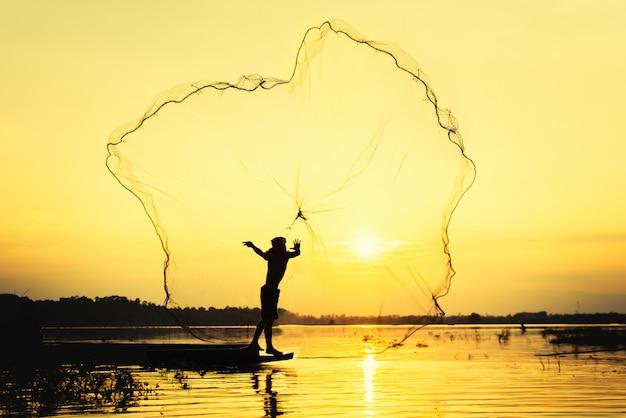 Vissersmens die onderdompeling het netto vissen bij meer met berg en blauwe hemelachtergrond werpen Premium Foto