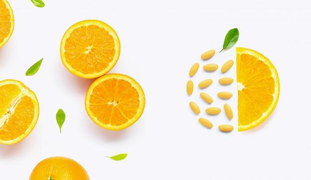Vitamine cpillen met verse oranje citrusvruchten die op wit worden geïsoleerd Premium Foto