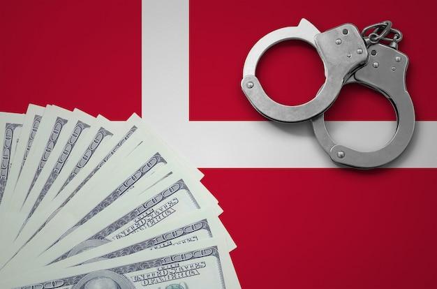 Vlag van denemarken met handboeien en een bundel dollars. het concept van illegale bankactiviteiten in amerikaanse valuta Premium Foto
