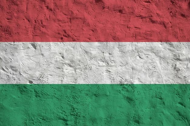 Vlag van hongarije afgebeeld in heldere verfkleuren op oude reliëf bepleistering muur. getextureerde banner op ruwe achtergrond Premium Foto