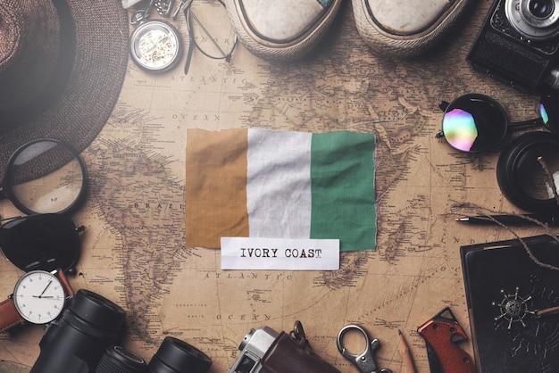 Vlag van ivoorkust tussen de accessoires van de reiziger op oude vintage kaart. overhead schot Premium Foto