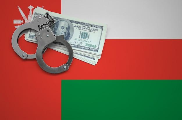 Vlag van oman met handboeien en een bundel dollars. het concept van het overtreden van de wet en dieven misdaden Premium Foto