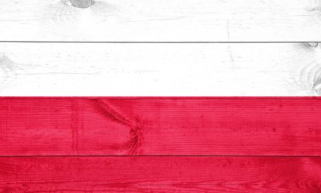 Vlag van polen afgebeeld in heldere verfkleuren op oude houten muur. Premium Foto