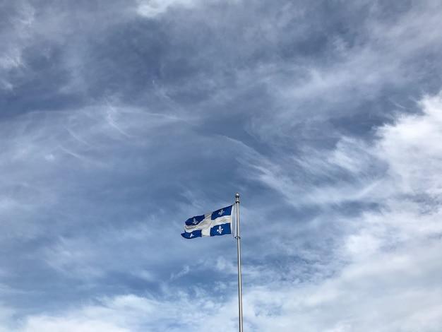 Vlag van quebec onder de prachtige wolken aan de hemel Gratis Foto
