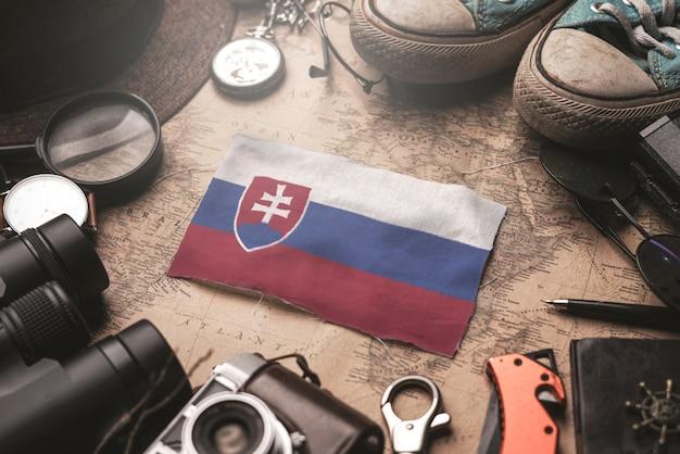 Vlag van slowakije tussen de accessoires van de reiziger op oude vintage kaart. toeristische bestemming concept. Premium Foto