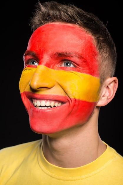 Vlag van spanje geschilderd op een gezicht van een lachende jonge man. Premium Foto