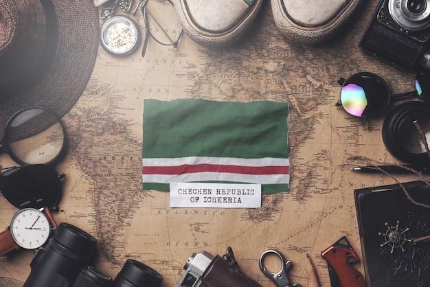 Vlag van tsjetsjeense republiek ichkeria tussen de accessoires van de reiziger op oude vintage kaart. overhead schot Premium Foto