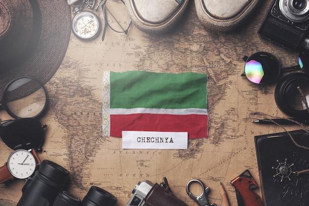 Vlag van tsjetsjeense republiek tussen accessoires van de reiziger op oude vintage kaart. overhead schot Premium Foto