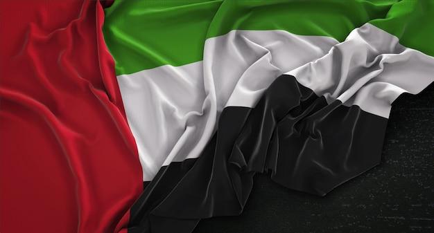 Vlag van verenigde arabische emiraten gerimpeld op donkere achtergrond 3d render Gratis Foto