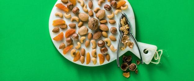 Vlag van verschillende soorten gedroogde vruchten en noten op een marmeren snijplank op een groene achtergrond Premium Foto