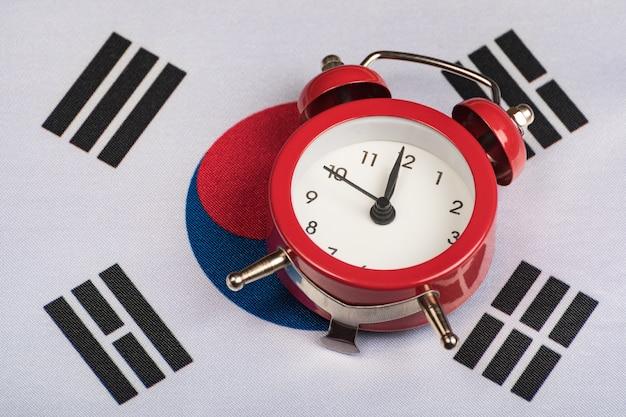 Vlag van zuid-korea en vintage wekker close-up. tijd om te reizen Premium Foto