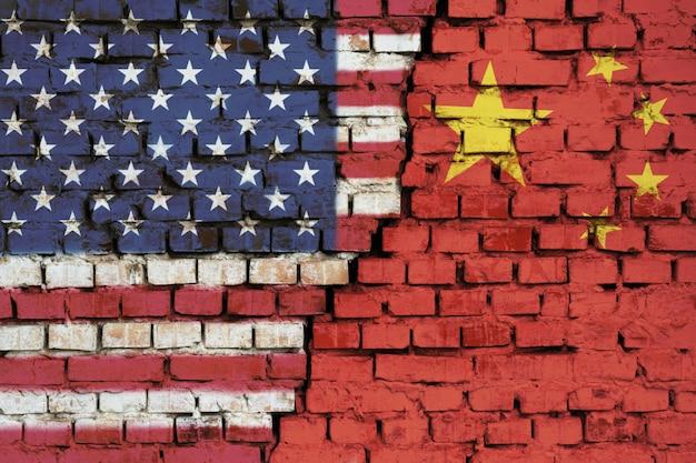 Vlaggen van verenigde staten en china op de bakstenen muur met grote barst in het midden Premium Foto