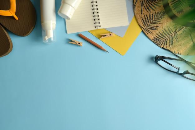Vlak leg, hoogste meningswerkruimte met hoed, zonblok op blauwe achtergrond. Premium Foto