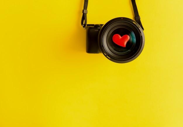 Vlak leg van mirrorless camera met lens en houd van rode harten op gele achtergrond Premium Foto