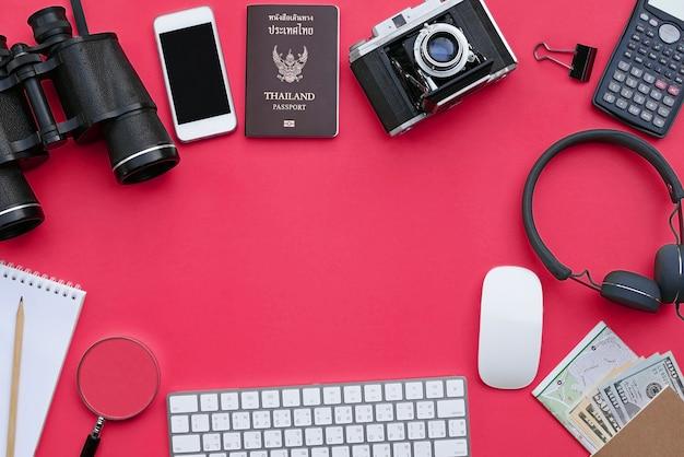 Vlak leg van reis en avonturentoebehoren op roze bureauachtergrond met copyspace Premium Foto