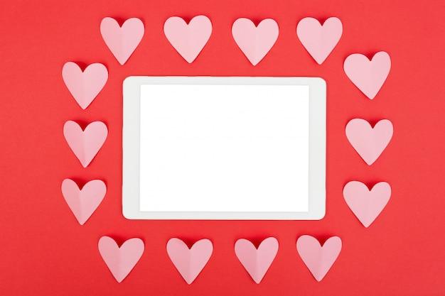 Vlak leg van tabletcomputer met het lege scherm op rode achtergrond met document harten Premium Foto