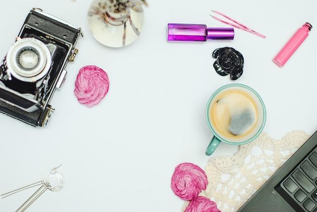 Vlakke bureau met koffie, zephyr, laptop, vintage camera en cosmetica Premium Foto