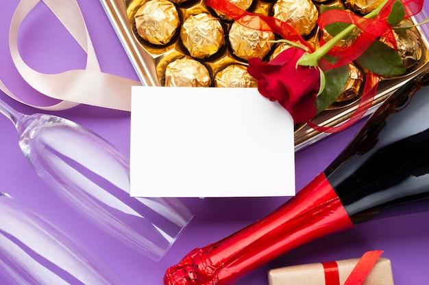 Vlakke decoratie met chocoladedoos en wijnfles Gratis Foto