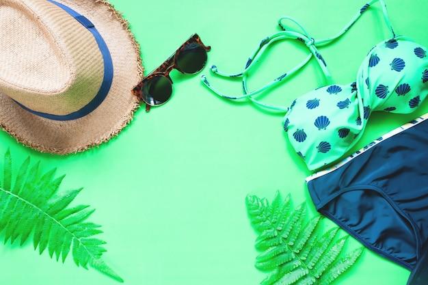 Vlakke lay-out van bikini en accessoires met varenbladeren op groene achtergrond, zomerconcept Gratis Foto