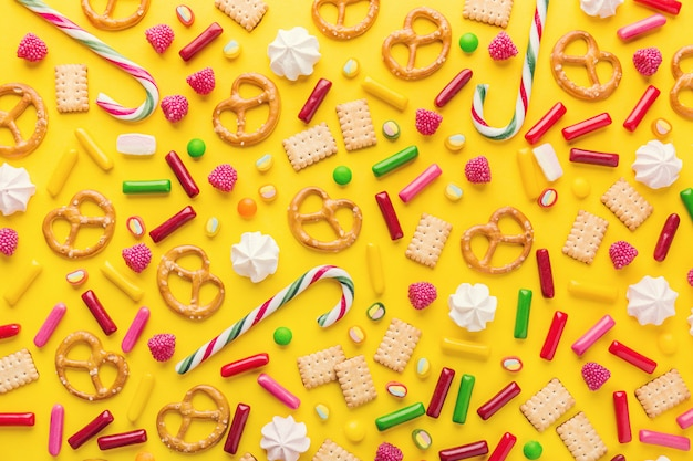 Vlakke snoepjes leggen op gele achtergrond Premium Foto
