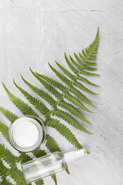 Vlakke weergave van een crème doos en fles op een blad en marmeren achtergrond Gratis Foto