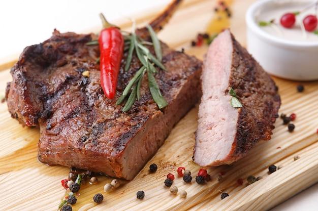 Vlees biefstuk met saus op een houten bord Premium Foto