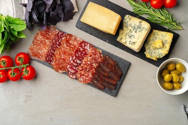 Vlees en kaas snijden op grijze achtergrond bovenaanzicht Premium Foto