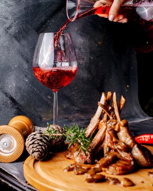 Vleesmaaltijd op het bruine houten oppervlak samen met rode wijn op het grijze oppervlak Gratis Foto