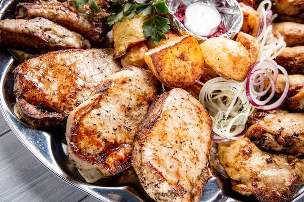 Vleesplaat met heerlijke stukken vlees, aardappelen, ui en kaars op witte houten tafel Premium Foto