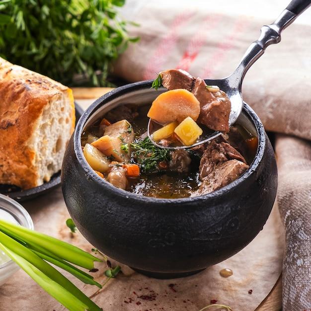 Vleessoep met champignons en groenten in een pot. macro weergave. Premium Foto