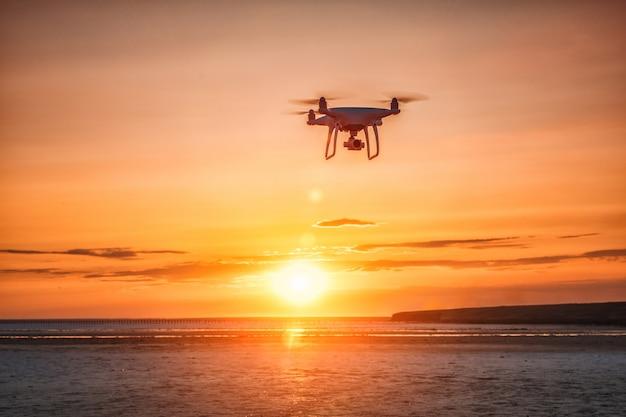 Vliegende drone op een achtergrond van zee zonsondergang Premium Foto