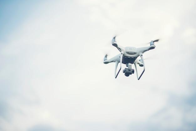 Vliegende drone tot blauwe hemelachtergrond Gratis Foto
