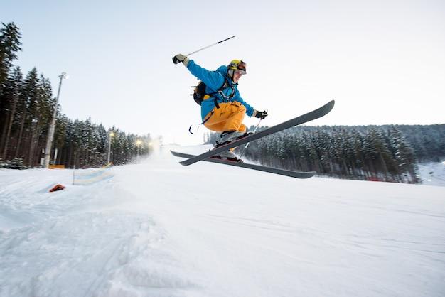 Vliegende skiërmens bij sprong van de helling van bergen die hoogspringen uitvoeren en ongerust over het landen met bos op achtergrond kijken Premium Foto