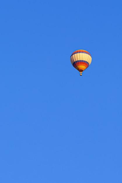 Vliegende veelkleurige ballon in de heldere blauwe hemel Gratis Foto