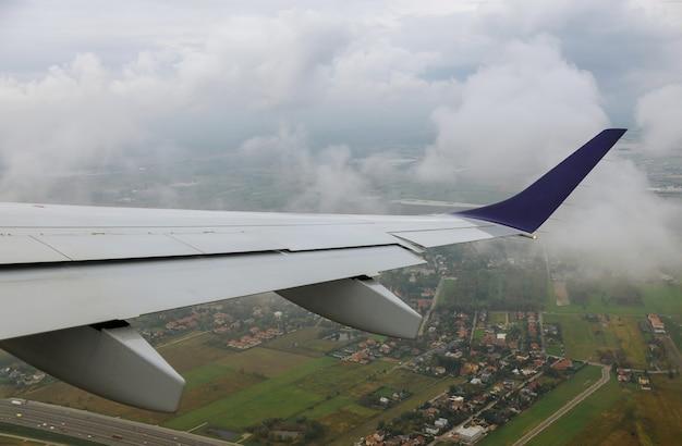 Vliegtuig in de lucht over groene velden de vleugel is zichtbaar door het raam luchtvervoer. Premium Foto