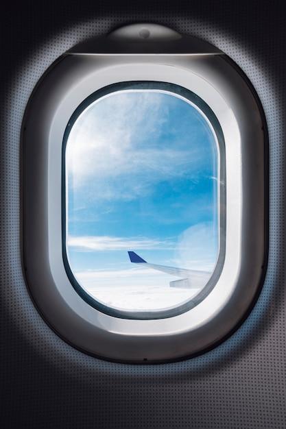 Vliegtuig raam met blauwe lucht en vleugel Gratis Foto