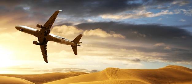 Vliegtuig vliegt over de woestijn op lage hoogte Premium Foto