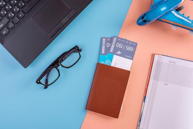Vliegtuig, vliegtickets, paspoort, laptop en telefoon met een bril. Premium Foto