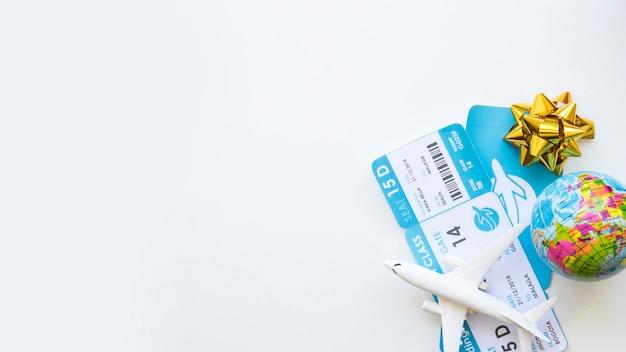 Vliegtuigkaartjes dichtbij stuk speelgoed bol en vliegtuigen Gratis Foto